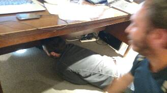 Jared and Julio lunge underneath the desk to examine the mystery insect. (Sorry, I only got a blurry action shot!)