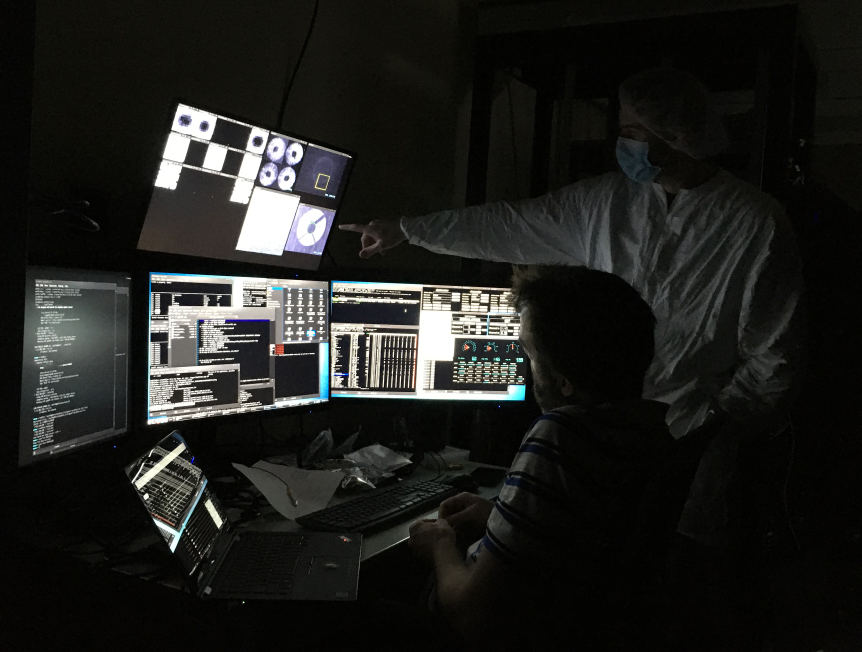 Alex Hedglen, in full cleanroom getup, points to an image of the MagAO-X pupil on one of Jared's five screens full of MagAO-X control software.