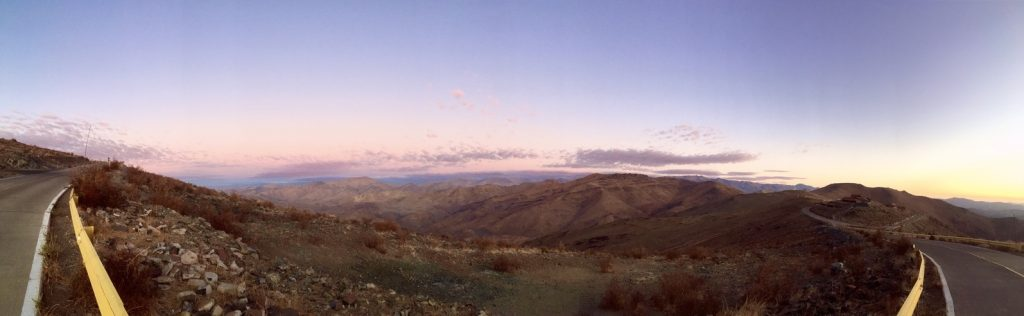 A panorama of the Chilean desert at sunset with scattered purple clouds