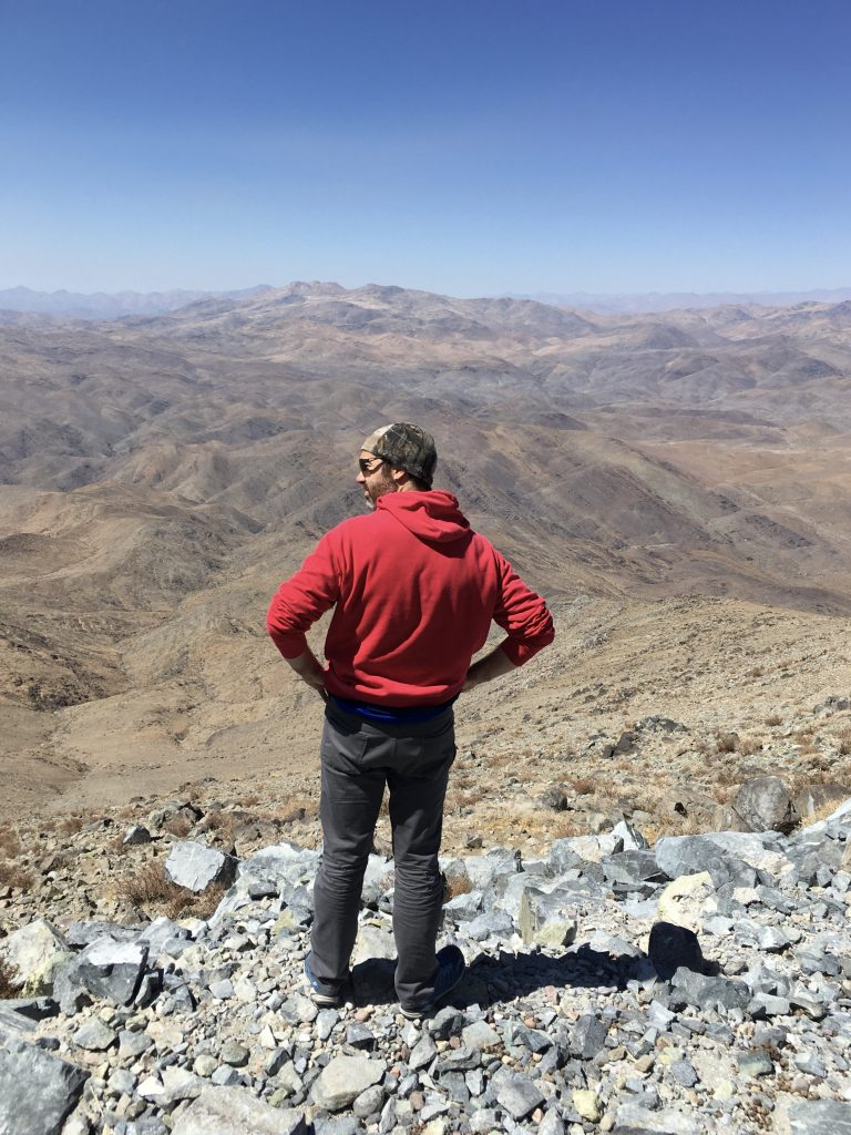 Dr. Jared Males stands on the mountain, overlooking the valley below.