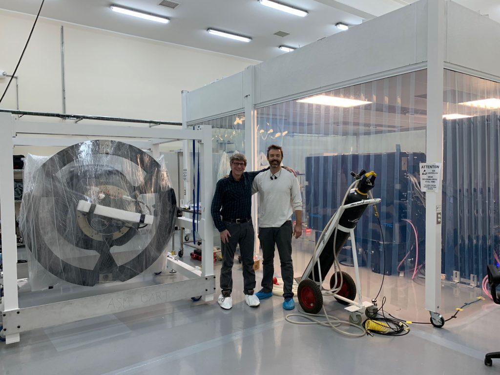 Jared Males and Laird Close, MagAO-X and MagAO PIs, stand next to their respective instruments in the LCO cleanroom