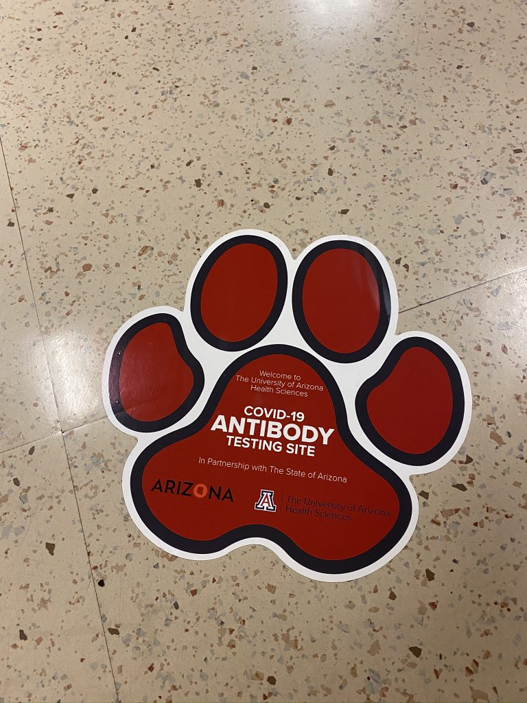 "A large paw print sticker modeled on a wildcat, affixed to a tile floor. It reads ""Welcome to The University of Arizona Health Sciences COVID-19 Antibody Testing Site In Partnership with The State of Arizona."" with logos for both Arizona and the University."