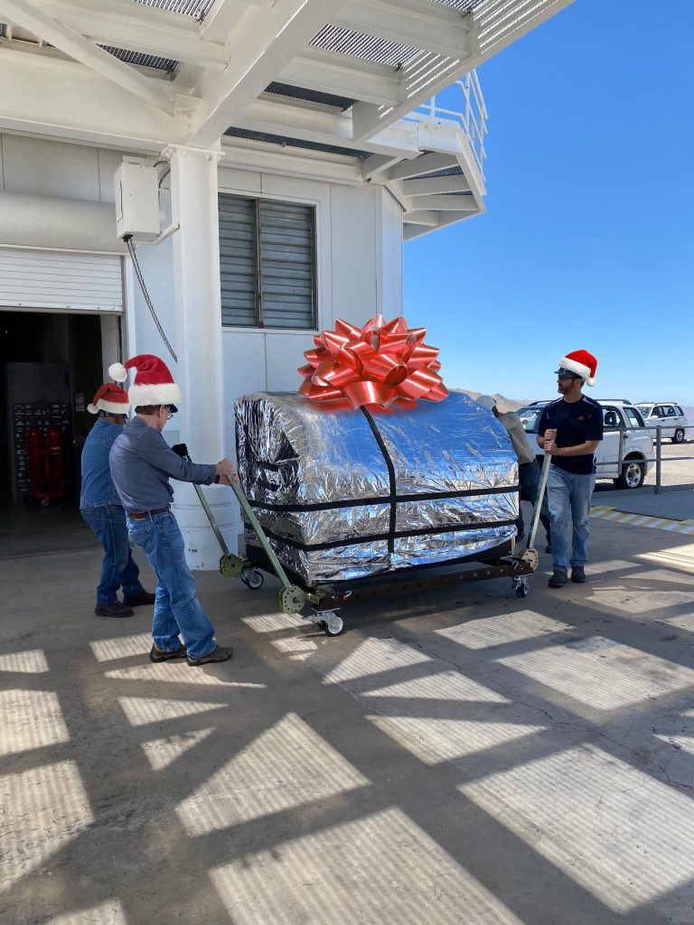 Jared, Laird, and a Las Campanas engineer move the foil-wrapped MagAO-X instrument on a cart. They're wearing photoshopped Santa Claus hats, and the MagAO-X instrument has a photoshopped bow on it.