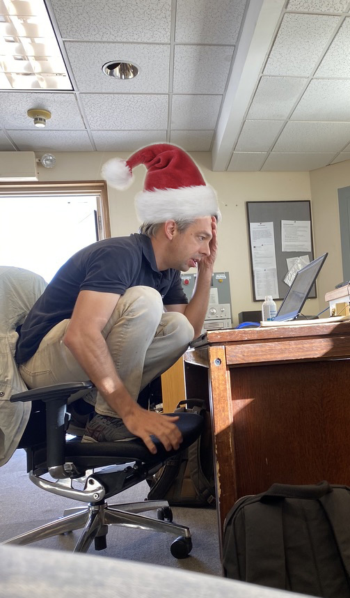 Olivier Guyon working on his laptop while perched awkwardly on a chair (with a photoshopped Santa Claus hat).