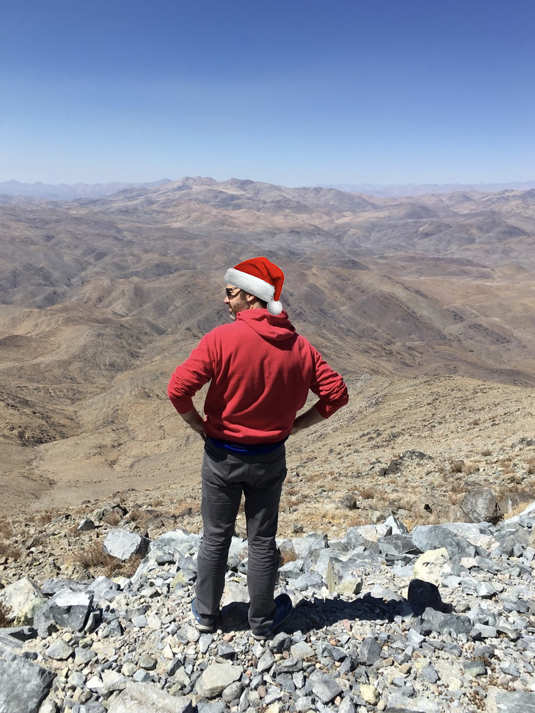 Jared surveys the rocky mountainside, looking into the distant Atacama with a photoshopped Santa Claus hat.